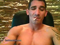 Tatooed tough guy smokes while strokes his cock