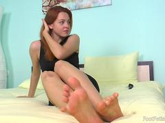 Candy works on a big dick with her feet